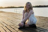 image of woman boots  - Portrait of a blond woman sitting on a deck wearing white lace dress and short black boots with lake behind her enjoying sun.