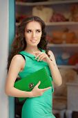picture of boutique  - Stylish woman in green dress with matching envelope bag in fashion boutique - JPG