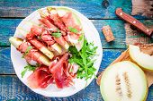 foto of melon  - salad of fresh melon with thin slices of prosciutto arugula leaves and balsamic sauce top view - JPG