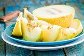 stock photo of muskmelon  - slices of fresh melon on a plate on a rustic blue table - JPG