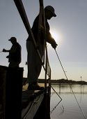 stock photo of crappie  - two men fishing on a dock in silhouette - JPG