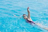 image of crawl  - Young girl in goggles and cap swimming front crawl stroke style in the blue water pool - JPG