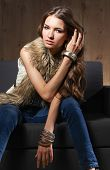 stock photo of vest  - Portrait of a elegant woman sitting on a black sofa wearing a blue jeans and fur vest - JPG