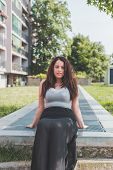stock photo of curvy  - Beautiful young curvy girl in tank top posing in an urban context - JPG