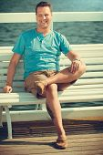 picture of sitting a bench  - Handsome man tourist sitting on bench on pier - JPG