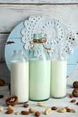 picture of caw  - Milk in glassware and walnuts on wooden background - JPG