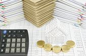 stock photo of piles  - Pile of gold coins in front of house with calculator on finance account have pile of envelope between paperwork as background - JPG