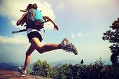 stock photo of cliffs  - young asian woman hiker running on mountain peak cliff - JPG