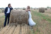 stock photo of hay bale  - Married couple staring one another deeply in love on a hay bale - JPG