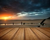 picture of shipwreck  - Dramatic sunset landscape over shipwreck on Rhosilli Bay beach with wooden planks floor - JPG