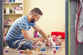 foto of diaper change  - Young hipster father changing nappy to his little baby daughter - JPG