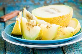 picture of honeydew melon  - slices of fresh melon on a plate on a rustic blue table - JPG