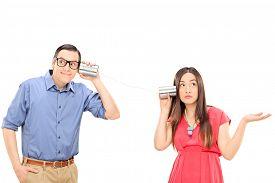 image of tin man  - Young couple talking through a tin can phone - JPG
