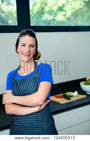 smiling woman preparing vegetables for dinner on a wooden chopping board