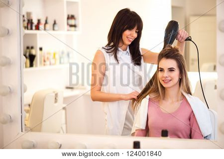 Women tricks. Cheerful beautiful woman sitting in the hairdressing salon while professional hairdresser drying her hair