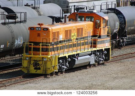San Diego- CIRCA February 2014: Bright Orange Engine 701 Amongst Black Railroad Cars Parked at the Railroad Yard in Downtown San Diego.