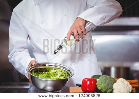 Chef putting oil on salad in commercial kitchen