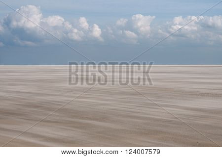 Empty windy beach with blue sky and clouds at Spiekeroog Germany