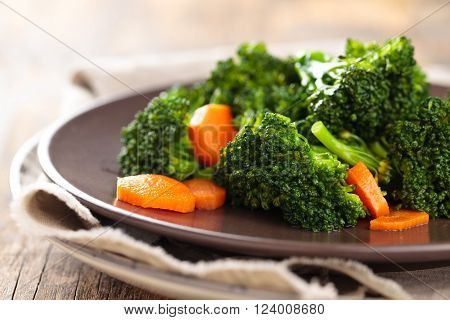 Closeup shot of steamed carrots and broccoli on plate.