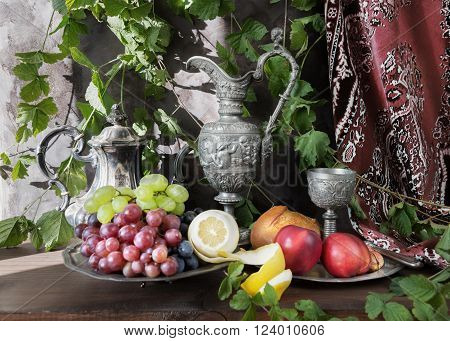 Still life in oriental style with antique pitcher and a goblets filled with wine grapes nectarines and lemon on a dark background covered with green plants