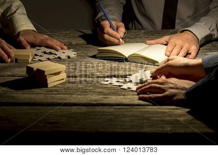 Team of three businessmen working on a project or assignment late at night with one making notes and the other two arranging puzzle pieces and wooden pegs on textured wooden desk.