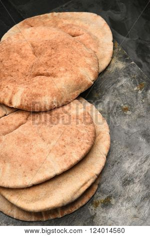 Vertical closeup of loaves of whole wheat pita bread on a gray slate surface and black background.