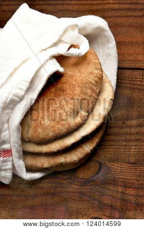 Whole wheat pita bread on a rustic wood table with copy space. The bread is wrapped in a towel and seen from a high angle. Vertical format.