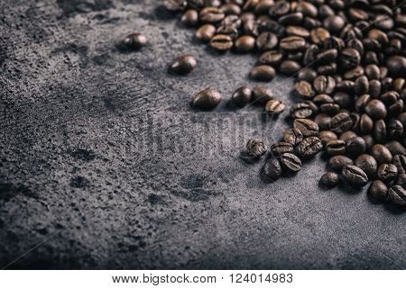 Coffee. Roasted coffee beans spilled freely on a concrete background.