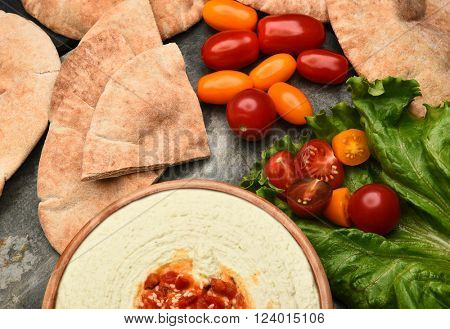 Top view of pita bread, edamame hummus, and medley tomatoes on a slate table.