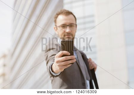 Businessman using mobile phone in the front of the business building. He is wearing suit an have the laptop bag over his shoulder