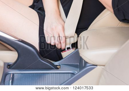 Women hand fastening seat belt inside car.