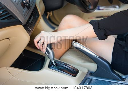 Hand driver shifting gear stick before driving car.