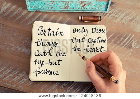 Retro effect and toned image of a woman hand writing on a notebook. Handwritten quote Certain things catch your eye but pursue only those that capture the heart as inspirational concept image