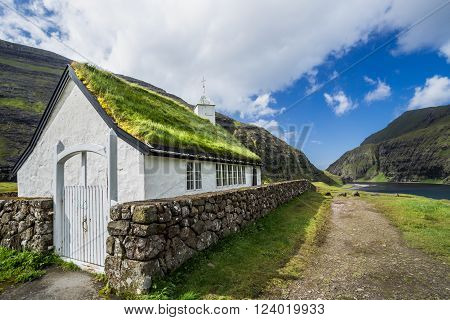 Panorama of a small village church in Saksun, nearby lake and a waterfall located on the island of Streymoy, Faroe Islands, Denmark