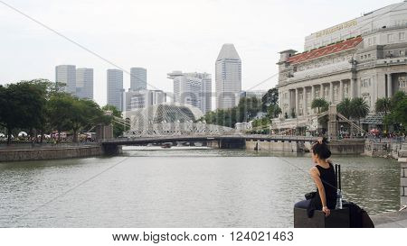 Singapore - Mar 26 2016: A young ladywas holding hair up sitting in Raffles Place by Singapore River and facing Marina Bay Area in light haze with a luggage and a bottle of water around.