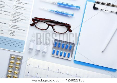 Doctor table with medicines, glasses and clipboard, top view
