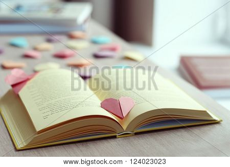 Books and heart shaped bookmarks on a wooden table