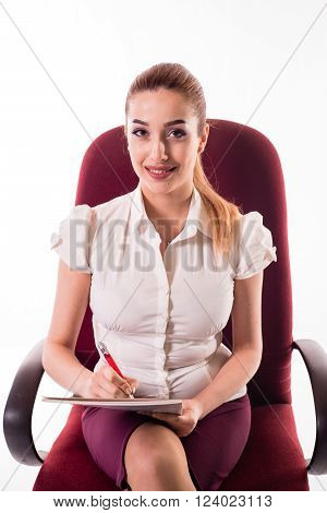 Cute office girl sitting on red chair with paper and pen in hand, and lovely smiling