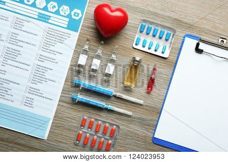 Doctor table with medicines, clipboard and red heart, top view
