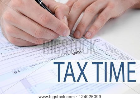 Tax Concept. Man filling American form of Individual Income Tax Return at the table