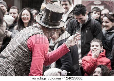 PARMA, ITALY - APRIL 2015: illusionist with magician's hat during street performance rear view