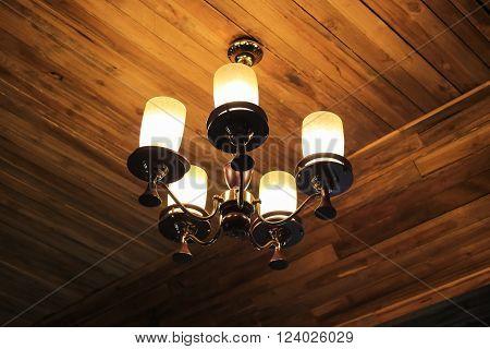 Vintage chandelier hanging on ceiling old wooden.