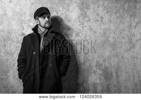image of a caucasian man with grungy blond hair dressed warmly in a stylish black trench coat and a funky hat and scarf for the cold winter