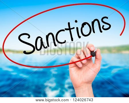 Man Hand Writing Sanctions With Black Marker On Visual Screen.