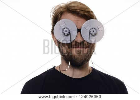 portrait of a man with glasses of tape reels of film on white background