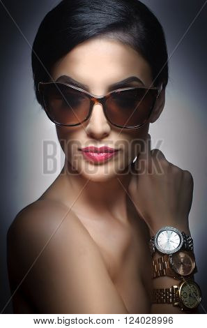 Woman with dark sun glasses and three watches on her arm. Beautiful woman portrait. Fashion art photo of young model with sun glasses. Elegant female portrait isolated. Romantic. Beauty. Modern style