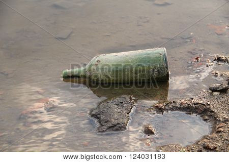 old glass bottle in the water at the bank of a pond or river