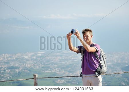 young smiling hiker with backpack making himself photo on the top of the mountain Vesuvius Italy