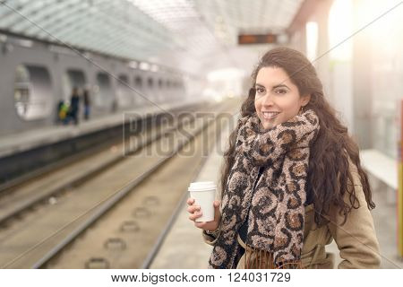 Smiling Woman In Coat With Coffee At Station