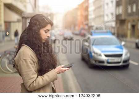 Brunette Woman Texting While Standing By Busy Street